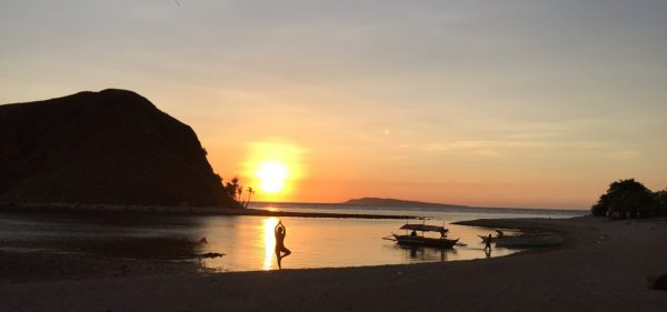 Practicing my yoga pose at sunset in Luyo beach.